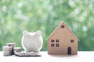 Modellhaus mit Sparschwein und Stapel von Münzen auf natürlichem grünem Hintergrund