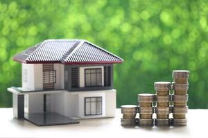 Modellhaus und Stapel von Geldmünzen auf natürlichem grünem Hintergrund
