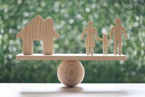Modellhaus und Modellfamilie auf Holzwaage mit natürlichem grünem Hintergrund