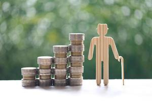 älterer Mann und Stapel von Münzen auf natürlichem grünem Hintergrund