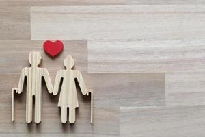 Holzausschnitt eines Paares und Herzform auf hölzernem Hintergrund