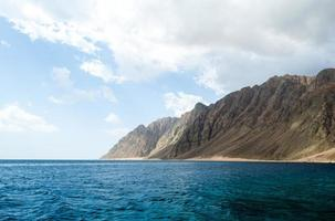 blaues Meer und hohe felsige Berge