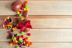 Schokoladeneier und Süßigkeiten auf einem braunen Hintergrund foto