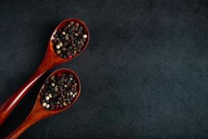 Mischung aus rotem und schwarzem Pfeffer in Holzlöffel auf schwarzem Hintergrund foto