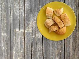 geschnittenes Brot auf einem gelben Teller auf einem hölzernen Tischhintergrund foto