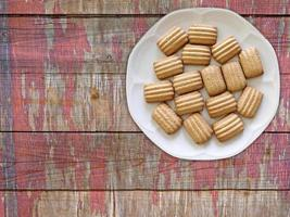gestreifte Kekse auf einem weißen Teller auf einem hölzernen Tischhintergrund foto