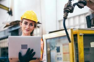 Frau im Schutzhelm hält einen Laptop foto