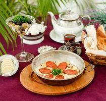 türkische Wurst mit Eiern in Stahlpfanne, Teekanne, Oliven und Brot