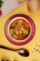 Gemüsesuppe mit Sesambrötchen und Holzlöffel foto