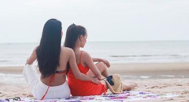 zwei schöne Frauen, die glücklich am Strand sitzen foto