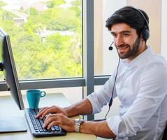 Geschäftsmann, der im Büro sitzt und glücklich lächelt foto