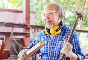 älterer asiatischer Zimmermann hält einen Hammer foto