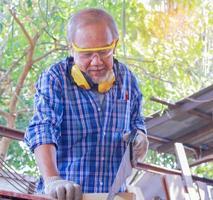 Der ältere asiatische Zimmermann verwendet Kreissägen, um Holz für Möbel zu verarbeiten foto