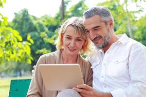 älteres Paar sitzt und entspannt sich im Park mit Tablet-Computer foto