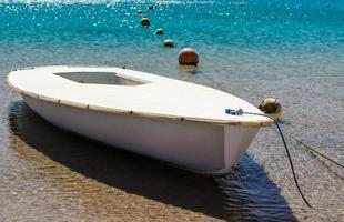 angebundenes Boot in türkisfarbenem Wasser