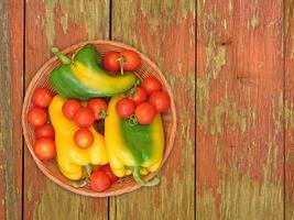grüne und gelbe Paprika und Tomaten auf einem Weidenteller auf einem hölzernen Tischhintergrund foto