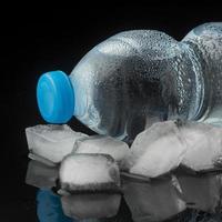 Eiswürfel und Flaschen Wasser, Vorderansicht foto