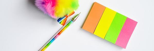 mehrfarbige Aufkleber und ein Stift auf weißem Hintergrund foto