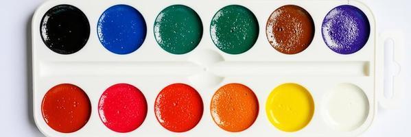 Schachtel Aquarellfarben auf weißem Hintergrund. Banner foto