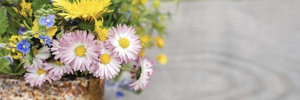 Ein Strauß Wildblumen aus Vergissmeinnicht, Gänseblümchen und gelbem Löwenzahn in voller Blüte in einem rustikalen Glas foto