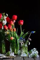 Stillleben mit Sträußen aus roten Tulpen, Feldgänseblümchen, Muskaris in Gläsern, Kirschblüten auf Holztisch auf dunklem Hintergrund foto