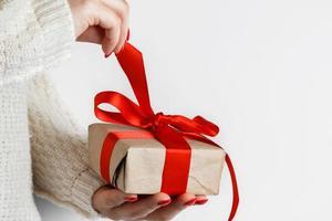 Geschenk mit einem roten Band in den Händen auf einem weißen Hintergrund