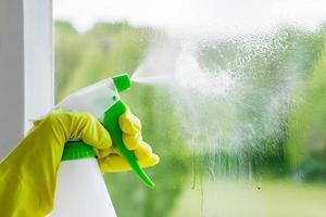 Eine Frau sprüht einen Reiniger auf Glas foto