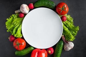 frisches Gemüse und weißer Teller auf dunklem Hintergrund foto