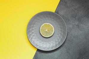 graue Platte mit Zitrone auf gelbem Hintergrund foto