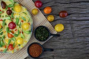 Nahaufnahme hausgemachte Gemüsepizza mit Kirschtomaten und Kräutern foto