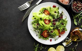frische grüne gemischte Salatschüssel mit Tomaten und Mikrogrün auf schwarzem Betonhintergrund foto