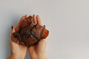Draufsicht des Schokoladenmuffins in den Händen der Frau foto
