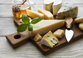 verschiedene Arten von Käse auf einem weißen hölzernen Hintergrund foto