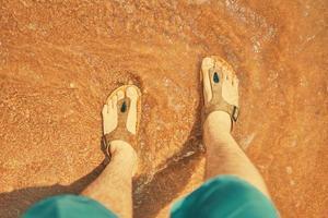 Person in Jeansshorts steht und schaut auf seine Füße in Sand, der vom Meer wäscht foto