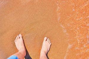 Männerfüße am Strand foto