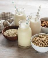 Flaschen mit verschiedenen Pflanzenmilch von Soja, Mandel und Hafer foto