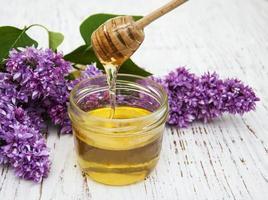 Fliederblumen mit Honig auf einem hölzernen Hintergrund foto