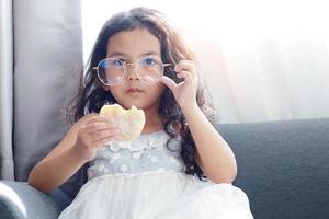 Mädchen sitzt auf dem Sofa und isst einen Donut foto