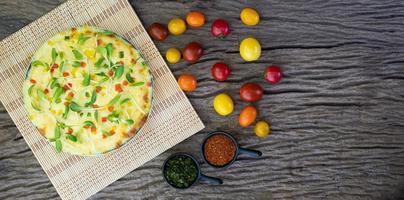 hausgemachte Gemüsepizza mit Kirschtomaten auf einem hölzernen Hintergrund foto