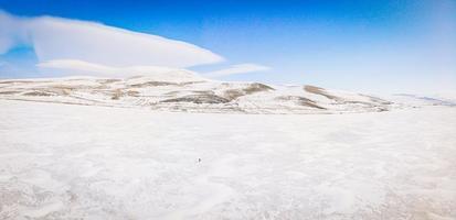 kleine Person steht auf einem zugefrorenen See, umgeben von Bergen foto