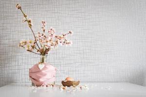 Frühlingsgänseblümchenblumen mit rosa Gesichtsmaske, die ein Osterei bedeckt foto