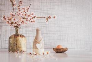 Frühling lebendiger weißer Tisch mit Gänseblümchen, Osterei und einem Herzanhänger foto