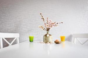 grüne und gelbe Tasse mit frischen Gänseblümchen in dekorativer Vase auf dem Tisch foto