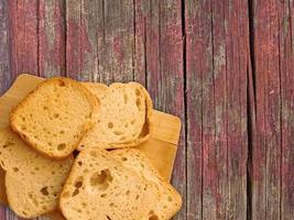 geschnittener Toast auf einem hölzernen Schneidebrett auf einem hölzernen Tischhintergrund foto