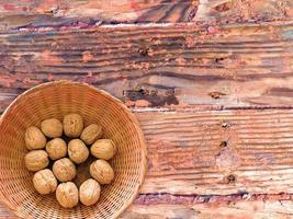 ganze Walnüsse in einer Weidenschale auf einem hölzernen Tischhintergrund foto