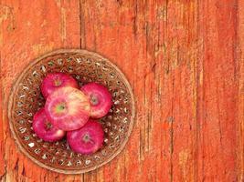 rote Äpfel auf einem Weidenteller auf einem hölzernen Tischhintergrund foto
