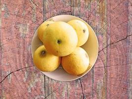 Orangen in einer Weidenschale auf einem hölzernen Tischhintergrund foto
