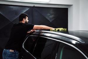 Mann reinigt die Karosserie mit einem Handtuch foto