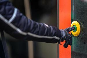 Hand drückt den Türöffnungsknopf im öffentlichen Verkehr foto