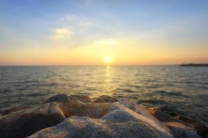 Sonnenuntergang am felsigen Ufer eines tropischen Strandes foto